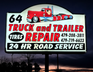 Sign at night in front of truck repair shop